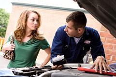 Mechanic: man explaining about oil filters Stock Photos