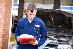 mechanic: reading diagnostic report - stock photo