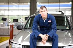 Mechanic: mechanic sits on suv hood Stock Photos