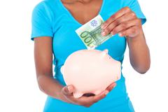 Black african american woman inserting a euro bill inside a smiling piggy ban Stock Photos