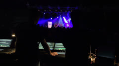Sound engineers on mixer look to the stage during live concert Stock Footage
