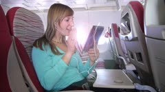 Woman is having video call over palmtop on the plane Stock Footage