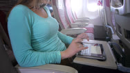 Stock Video Footage of Young woman typing on digital tablet on the plane