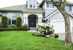 Residential home in mid spring season with blooming flowers and plush green g Stock Photos