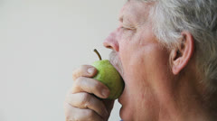 Man tries to eat unripe pear Stock Footage