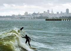 silhouetted surfers in the san francisco bay - stock photo