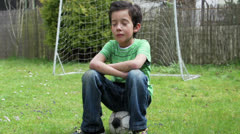 Stock Video Footage of Sad boy sitting on soccer ball