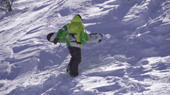 SLOW MOTION: Snowboarder going uphill - stock footage