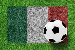 soccer ball on flag of italy as painting on green grass background - stock photo