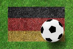 Soccer ball on  flag of germany as painting on green grass background Stock Photos