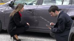 Woman and insurance agent discussing car damage - stock footage