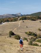 Man walking along a mountain path Stock Photos