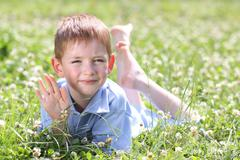 5 years old child lying on the grass. Stock Photos