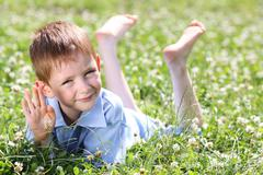 5 years old child lying on the grass. - stock photo