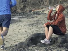 Woman resting after jogging on the beach, slow motion, shot at 240fps NTSC Stock Footage