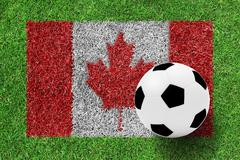 soccer ball on canada flag as a painting on green grass - stock photo