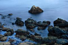 long exposure of sea over rocks - dreamy feel - stock photo