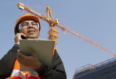 construction worker with crane in background - stock photo