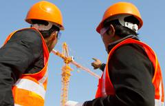 Site manager with safety vest discussion under construction Stock Photos