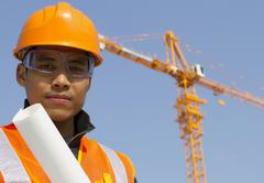close up site manager with safety vest under construction - stock photo
