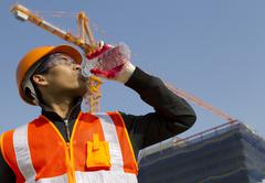 worker man  as he drinks from a plastic water bottle - stock photo