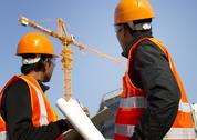 Construction workers with crane in background Stock Photos