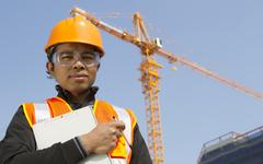 Construction worker with crane in background Stock Photos