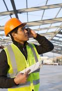 Engineer construction talking mobile phone under new building Stock Photos