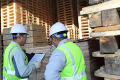 two workers talking beside on stacking pallet - stock photo