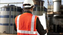 Stock Photo of engineer on location site with blueprint