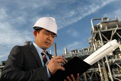 businessman with oil refinery background - stock photo