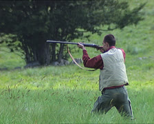 Hunter shooting with rifle close Stock Footage