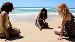 Friends painting smiley shape in sand Stock Footage