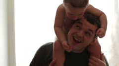 Stock Video Footage of Two year old son is sitting on the father's shoulders.