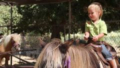 Pretty Latino baby sits on the horse Stock Footage