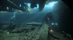 Divers inside the ship wreck Stock Footage