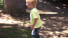 White Latino kid walks along the ground to reach his mom Stock Footage