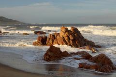 beachfront with sharp rocks - stock photo