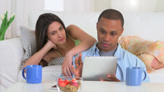 Interracial couple using tablet while eating breakfast Stock Footage
