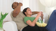 Happy African American and Caucasian couple using smart phone and eating popcorn Stock Footage