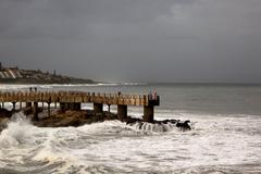 stormy weather and waves at concrete jetty - stock photo