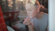 Stock Video Footage of Through the window portrait of girl making her lips shine.