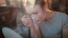 Through the window portrait of a beautiful girl applying mascara to her - stock footage