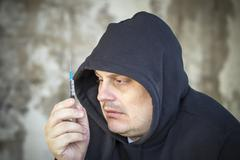 Drug addict men looks at the syringe in the hands Stock Photos