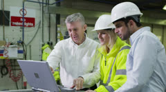 3 workers in a warehouse with a laptop are discussing their work. - stock footage