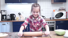 Little girl kneading dough with rolling pin on table Stock Footage