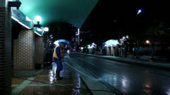 City worker rinsing the side walk at a bus station Stock Footage