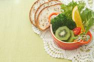 Stock Photo of fusion food, fruit and vegetable salad in colorful cup with whole wheat bread