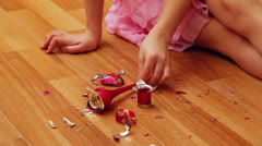 Little girl takes fragments of broken toy from parquet floor Stock Footage