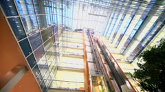 Two elevators ride at multilevel building with transparent roof Stock Footage